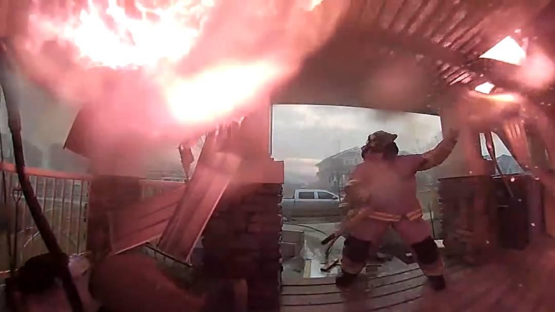 Die Einsatzkräfte schlagen das brennende Vordach herunter, um zu verhindern, dass die Flammen auf das Haus übergreifen.
