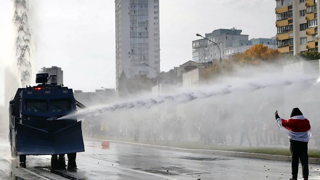 dpatopbilder - Polizisten setzten einen Wasserwerfer gegen Demonstranten ein. Trotz eines Großaufgebots an Sicherheitskräften haben Zehntausende Menschen gegen den autoritären Staatschef Lukaschenko demonstriert. Foto: Uncredited/AP/dpa