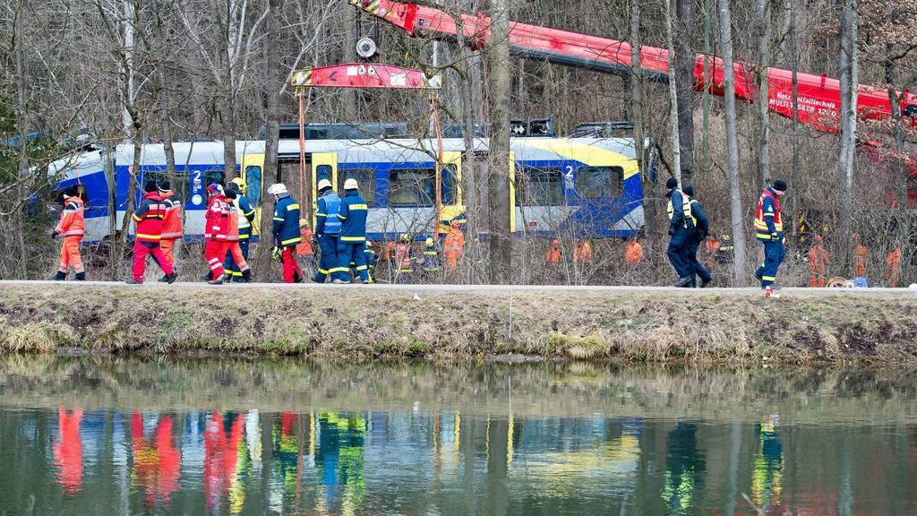 epa05154295 Task force units watch a crane lift a train car at the site of the train accident in Bad Aibling, Germany, 11 February 2016. Two Meridian commuter trains of the private railway company Bayerische Oberlandbahn collided head-on at high speed near Bad Aibling on the single-track line between Holzkirchen and Rosenheim. At least 10 people were killed and 80 injured in the accident as the two trains carrying a total of 150 people impacted on 09 February 2016.  EPA/PETER KNEFFEL