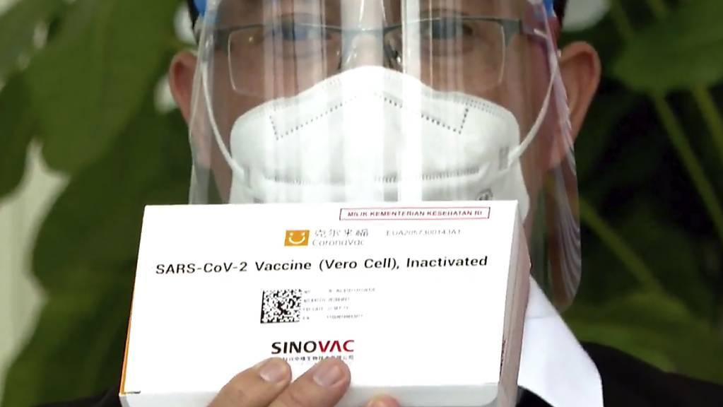Ein medizinischer Mitarbeiter des Gesundheitsministeriums zeigt eine Schachtel eines in China hergestellten Corona-Impfstoffs, bevor Indonesiens Präsident Widodo im Merdeka-Palast seine erste Impfdosis erhält.