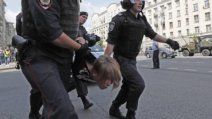 Russische Polizisten führen einen Kundgebungsteilnehmer vor dem Moskauer Rathaus ab.