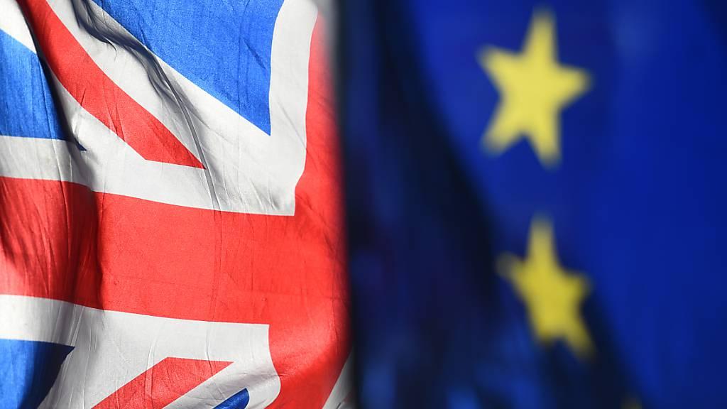 ARCHIV - Eine Flagge der Europäischen Union und eine Flagge von Großbritannien wehen vor dem Parlament in Westminster. Foto: Kirsty O'connor/PA Wire/dpa