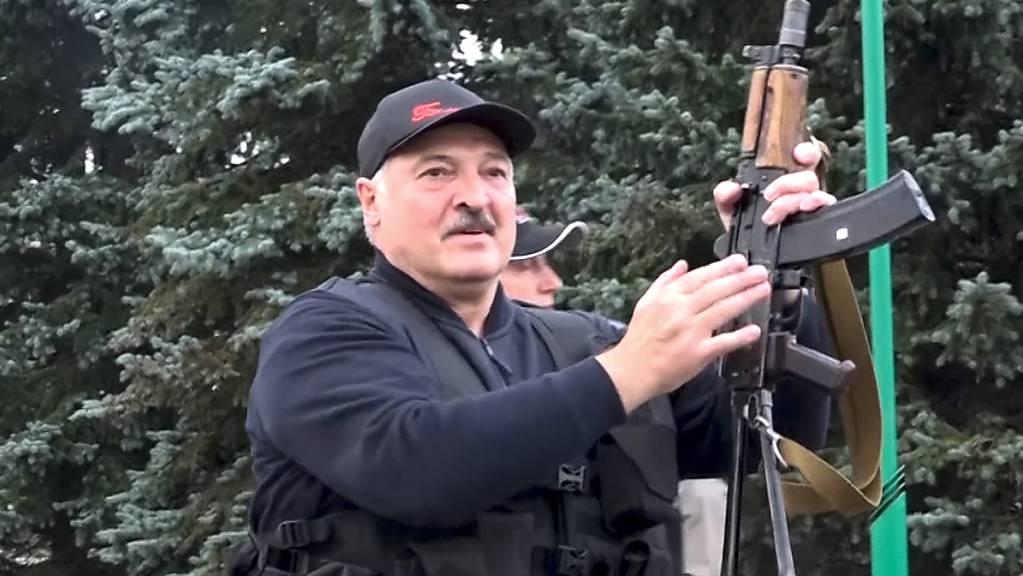 Der belarussische Diktator Alexander Lukaschenko hantiert mit einem Maschinengewehr. (Archivbild)