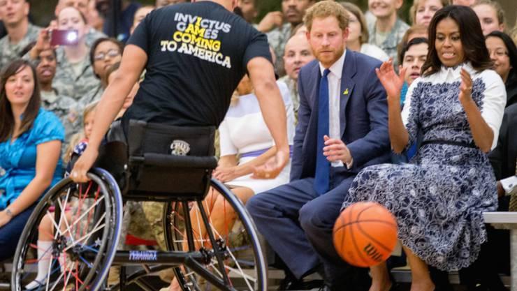 Michelle Obama und Prinz Harry nahmen am Spielfeldrand auf einer Metallbank Platz und sahen dem Basketball zu.