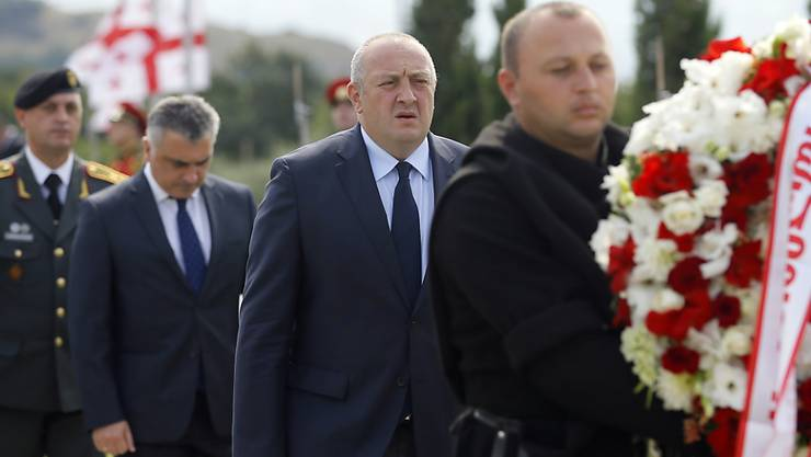 Präsident Giorgi Margwelaschwili (M) legte auf einem Friedhof bei Tiflis einen Kranz zum Gedenken an die getöteten georgischen Soldaten nieder.