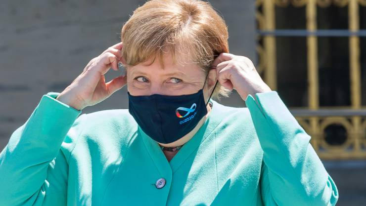 Bundeskanzlerin Angela Merkel (CDU) setzt sich vor Beginn der bayerischen Kabinettssitzung auf der Insel Herrenchiemsee ihre Mund-Nase-Schutzmasken auf. Foto: Peter Kneffel/dpa/Pool/dpa