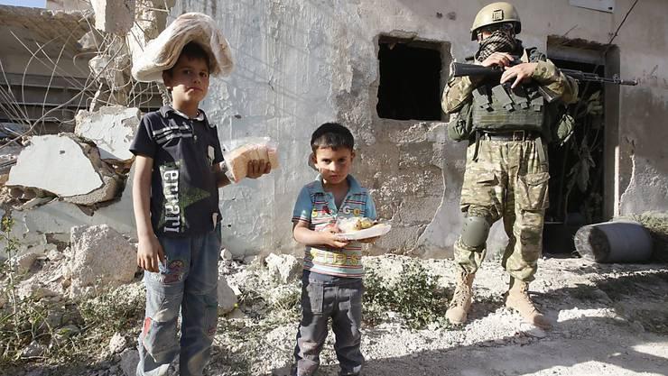 Syrische Kinder erhalten Brot und Süssigkeiten aus einer russischen Hilfslieferung in der Provinz Hama. Für die umkämpfte Stadt Aleppo hat das Regime einer Feuerpause zugestimmt.
