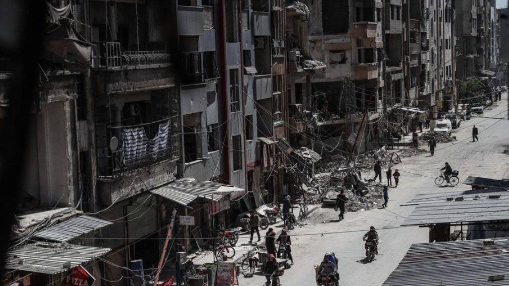 Menschen auf einer Strasse in Duma, Ost-Ghuta. Die syrische Regierung soll gemäss Angaben der russischen Armee mittlerweile die Kontrolle über ganz Ost-Ghuta übernommen haben. (Archiv)