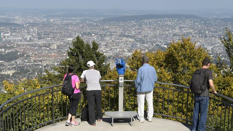 Personen betrachten den Blick auf die Stadt Zuerich vom Zuercher Hausberg Uetliberg (871 m)