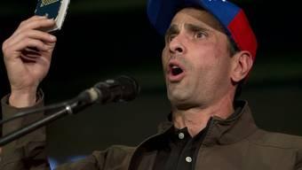 ARCHIV - Henrique Capriles, Oppositionspolitiker in Venezuela, spricht zu seinen Anhängern und hält dabei eine Miniaturausgabe der Verfassung von Venezuela in die Höhe. Foto: Ariana Cubillos/AP/dpa