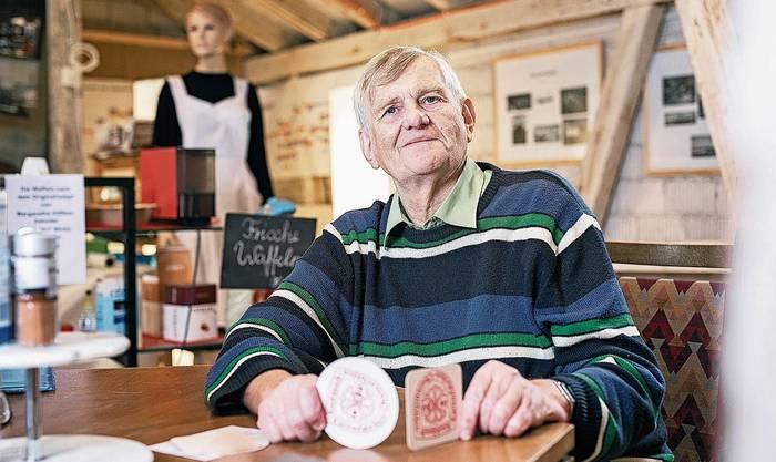 Gemeindearchivar Christian Heilmann zeigt die Karton-Bierdeckel mit dem Knoblauch-Logo.