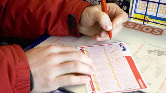 Ein Mann füllt einen Lotto-Schein aus (Symbolbild)