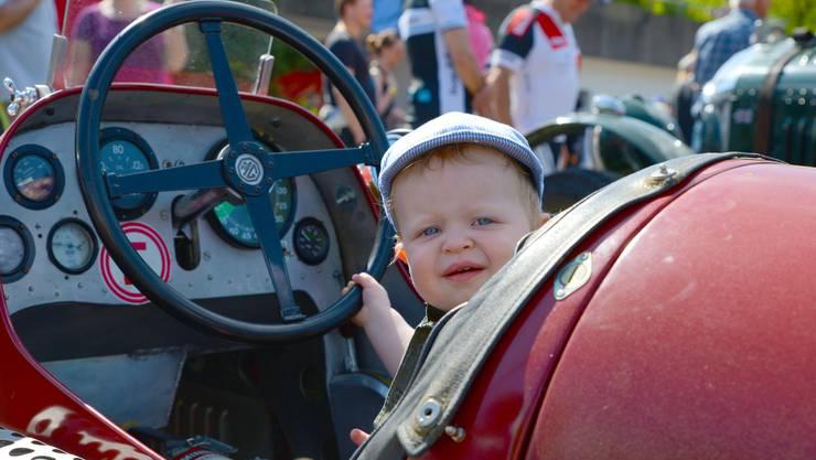 Rennsport fasziniert: Ein junger Fan darf sich probehalber ins Cockpit setzen.