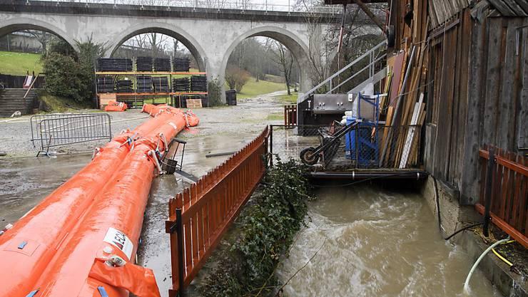 Die Feuerwehr installierte an der Asse im Bezirk Nyon schwimmende Absperrungen, um weitere Schäden an Häusern und Schuppen zu verhindern.