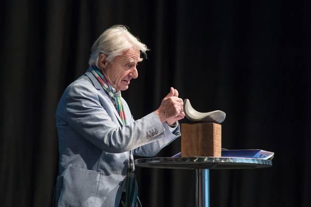 Emil Steinberger freut sich über das Kunstobjekt aus geöltem Nussholz und einem Findlings-Stein von Saskya Germann, das Teil des Preises ist.