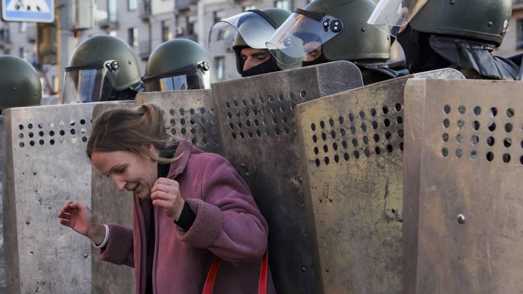 Eine Frau steht bei einer Kundgebung der Opposition, um gegen die offiziellen Ergebnisse der Präsidentschaftswahlen zu protestieren, vor Polizisten mit Schilden. Foto: Uncredited/AP/dpa