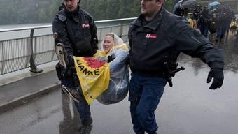 Abtransport einer Demonstrantin durch die Polizei im strömenden Regen