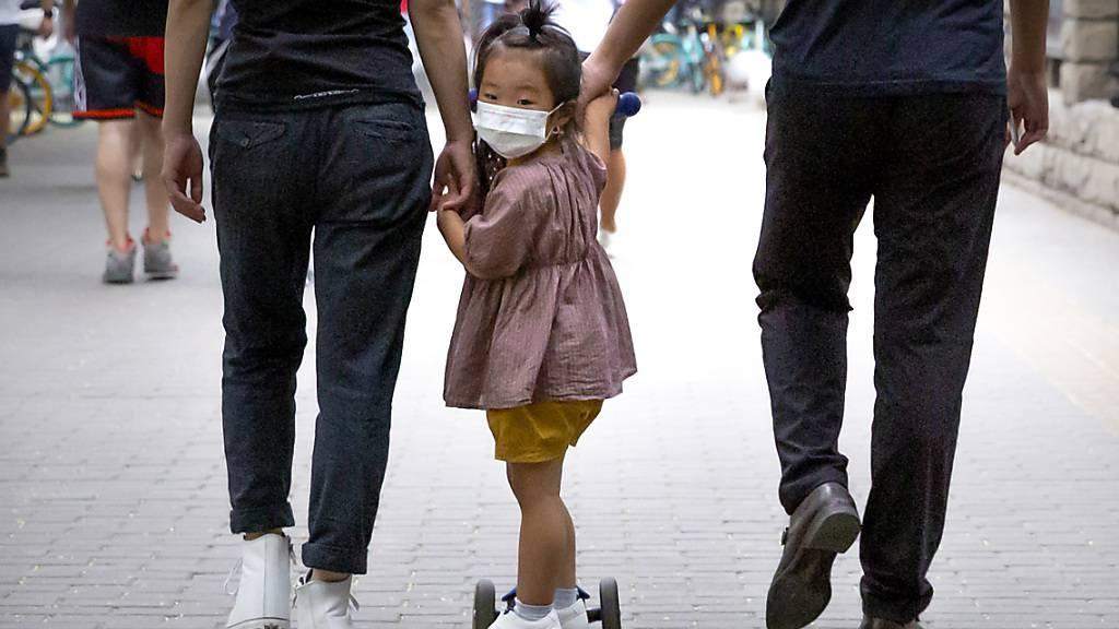 ARCHIV - Ein kleinen Mädchen mit Mundschutz wird auf ihrem Roller über einen Gehweg gezogen. Foto: Mark Schiefelbein/AP/dpa