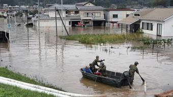 Rettungskräfte helfen Betroffenen in einem überschwemmten Wohngebiet in der japanischen Region Fukushima.