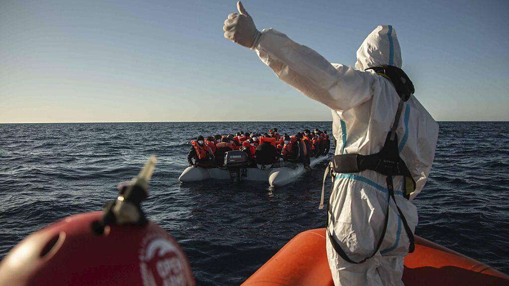 ARCHIV - Ein Mitarbeiter NGO «Open Arms» vor der libyschen Küste gestikuliert in Richtung eines überfüllten Schlauchbootes, auf dem sich Migranten aus verschiedenen afrikanischen Ländern befinden (Bild vom 06.02.). Hilfsorganisationen fahren immer wieder  aufs Meer, um Menschen vor dem Ertrinken zu retten. Foto: Pablo Tosco/AP/dpa