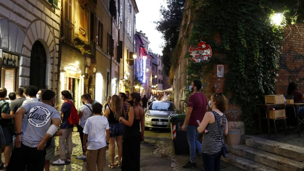 ARCHIV - Gäste stehen mit Mundschutzen vor einem Restaurant an. Italiens Regierung bereitet nach Medienberichten eine erneute Verschärfung der Anti-Corona-Maßnahmen vor, um den steilen Anstieg der Ansteckungszahlen zu bremsen. Foto: Cecilia Fabiano/LaPresse via ZUMA Press/dpa