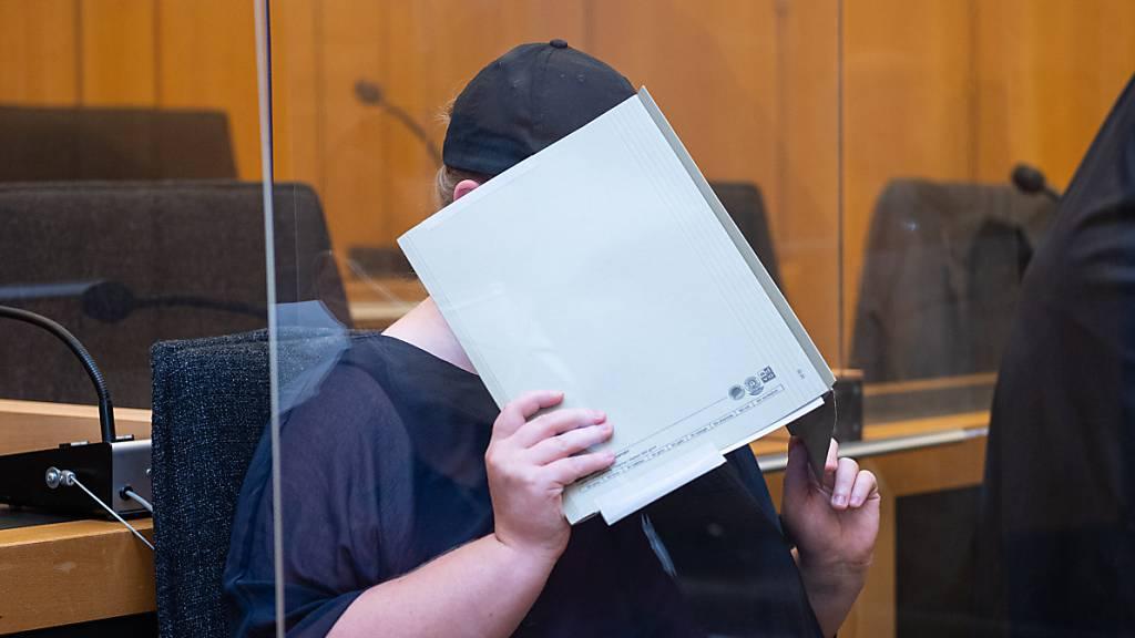 ARCHIV - Zu Beginn des Prozesses im Missbrauchskomplex Münster sitzt die Mutter eines Opfers im Landgericht Münster und verdeckt ihr Gesicht mit einer Mappe. Foto: Guido Kirchner/dpa