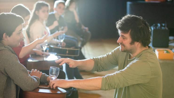 Musiklehrer Gabriel Stampfli erzeugt hohe und tiefe Klänge mit den Vibrationen eines Glases.