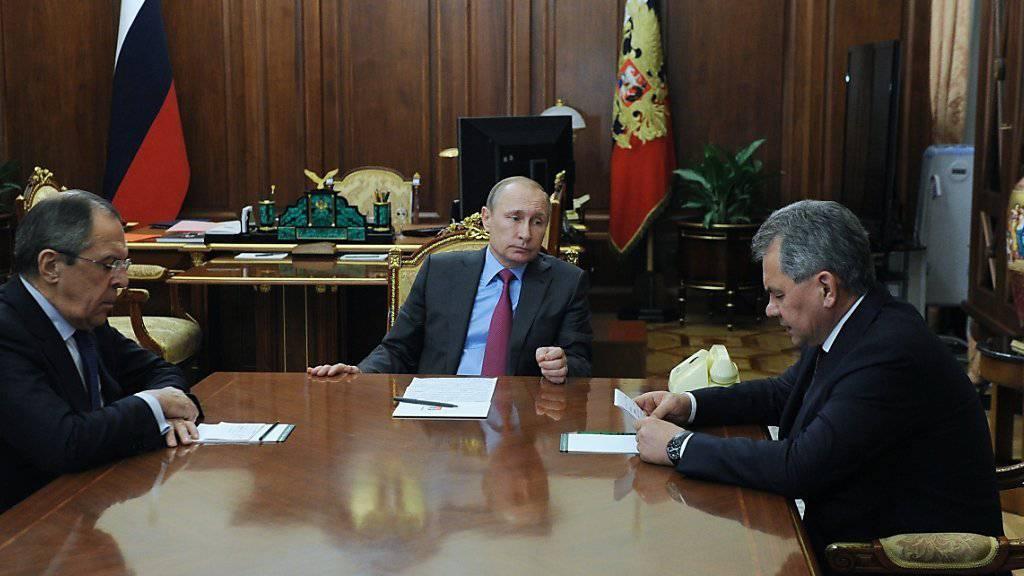Präsident Putin (M.) informiert seine Minister Lawrow (l.) und Schoigu über den Entscheid, dass die russischen Truppen aus dem Bürgerkriegsland Syrien zurückbeordert werden sollen.