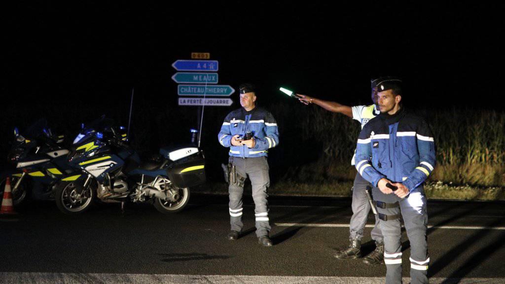 Polizisten haben eine Strasse in der Nähe des Tatorts in Sept-Sorts gesperrt.