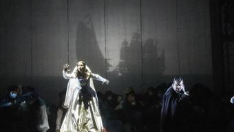 """Die Dienerin Emilia (Sarah Mehnert) und die Zyprioten erwarten die Ankunft von Otello: Die Berner Inszenierung der Verdi-Oper """"Otello"""" rückt die Dienerin ins Zentrum; aus ihrer Perspektive wird das Drama erzählt."""