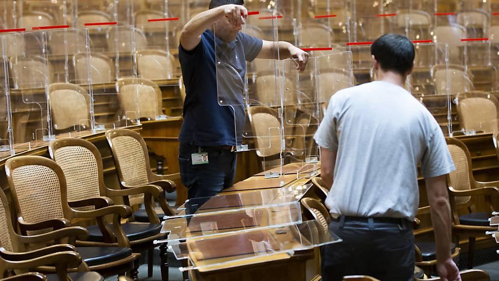 Weil im Parlament die Zertifikatspflicht gilt, räumen Mitarbeiter der Parlamentsdienste die Plexiglasscheiben im Nationalrat weg.