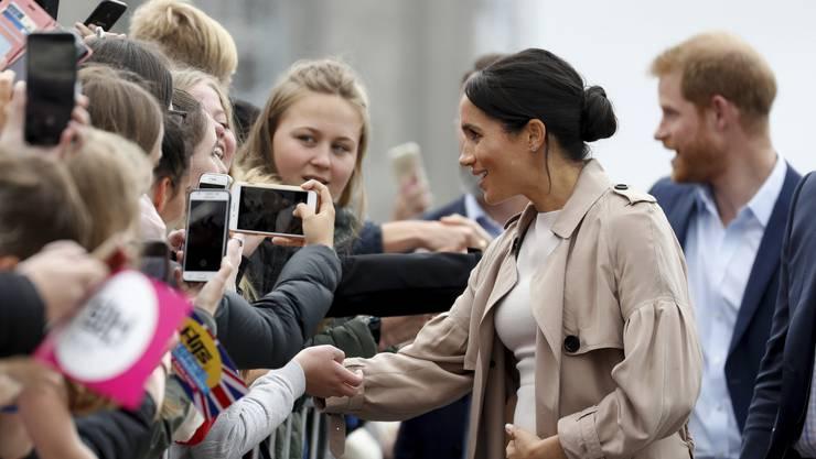 Prinz Harry (hinten) und seine Frau Meghan grüssten am Dienstag die Bevölkerung in Auckland.