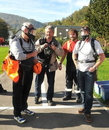Besucher streifen sich die Atemschutzmaske über, um eine simulierte Bergung vorzunehmen.