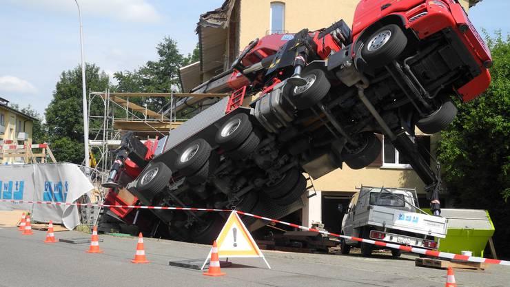Wie ein riesiger Käfer liegt der schwere Lastwagen auf der Achse.