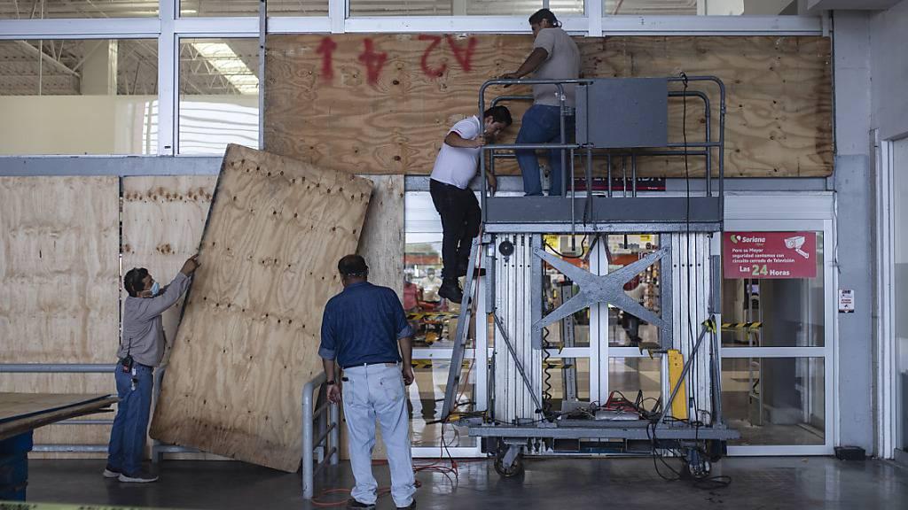Arbeiter bringen wegen des Hurrikans «Grace» Schutzwände an in der mexikanischen Stadt Boca del Rio.
