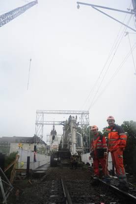 Die Bauarbeiter Huseyn Kidic (l.) und Marco Grgic lassen sich vom Regenwetter nicht die Laune verderben.