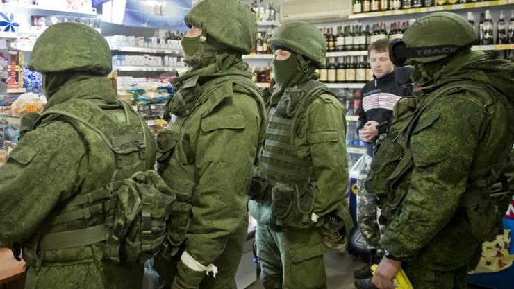 So genannte grüne Männchen, Soldaten ohne Hoheitsabzeichen und darum national nicht identifizierbar, in einem Geschäft in der Ost-Ukraine im März 2014. Später gab der russische Präsident Wladimir Putin zu, dass es sich bei solchen Soldaten auf der Krim um russische Armeeangehörige gehandelt habe.