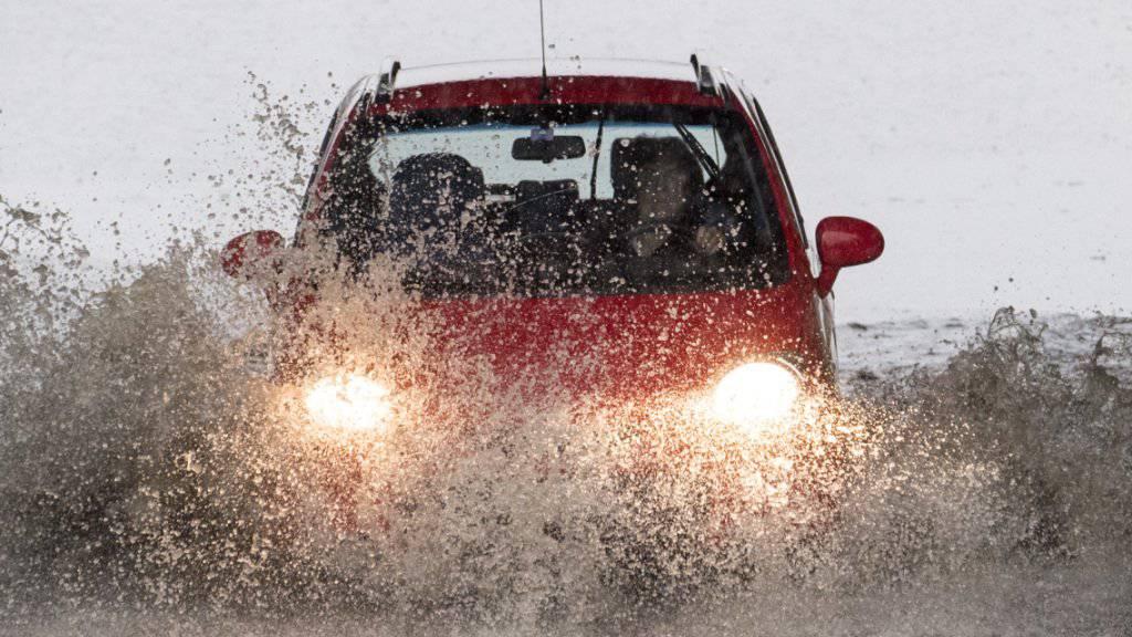 Eine Autofahrerin auf einer überfluteten Strasse. Frauen sind gemäss einem Unfallexperten generell vorsichtiger unterwegs und scheuen das Risiko. (Archivbild)
