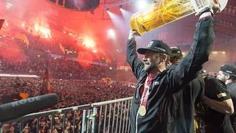 SCB-Captain Martin Plüss präsentiert den Fans in der Berner Eishockey-Arena nach der Rückkehr aus Zug den Meisterpokal