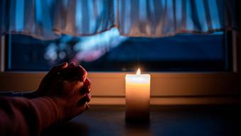 Eine Frau betet Mitte März im deutschen Oberhausen vor einer Kerze.