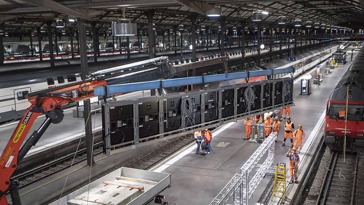 Ein Kran hievt die Anzeigetafeln bei der Stirn des Luzerner Bahnhofs zur Montage in die Höhe.