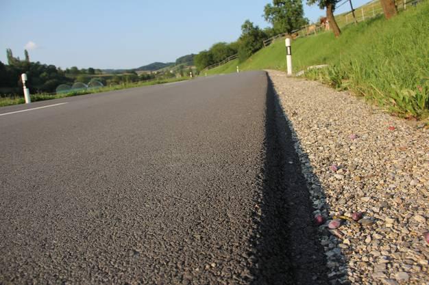 Strasse im Ausserortsbereich zwischen Bözen und Elfingen nach der Sanierung mit grossem Niveauunterschied zwischen Deckbelag und Bankett und ohne Seitenlinie.
