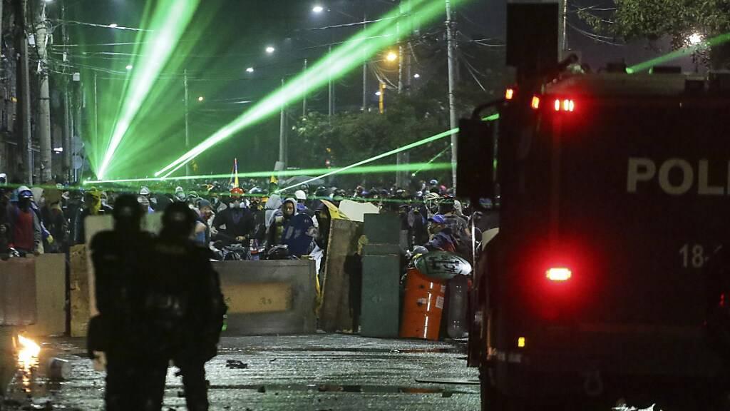 Anti-Regierungs-Demonstranten zielen während eines Protests mit Lasern auf Polizisten. Foto: Ivan Valencia/AP/dpa