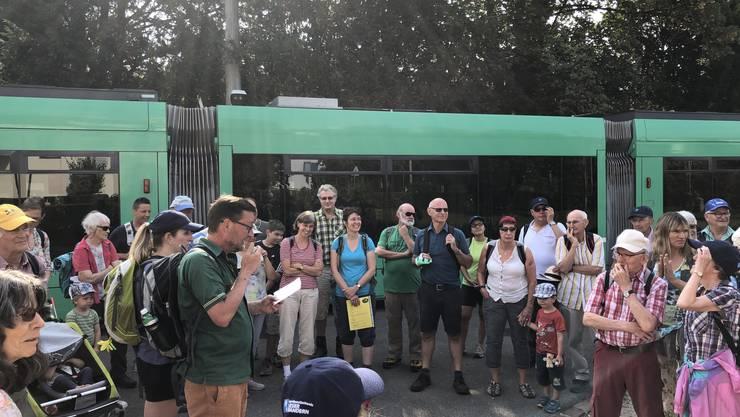 bz-Chefredaktor David Sieber begrüsst die Wandernden an der Tramhaltestelle Neuweilerstrasse in Basel.