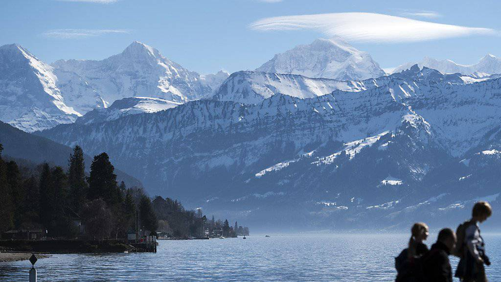 Frühlingshafte Bedingungen im Berner Oberland: Sonnenhungrige geniessen das milde Wetter mit Blick auf Eiger, Mönch und Jungfrau im Schadaupark in Thun BE.