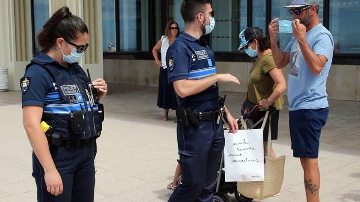 Polizeibeamte weisen Passanten auf das Tragen einer Mund-Nasen-Bedeckung hin. Im Kampf gegen Corona gilt in weiteren französischen Gemeinden jetzt eine Maskenpflicht im Freien. Foto: Bob Edme/AP/dpa