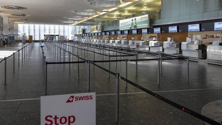 Die Absperrbänder weisen auch Menschenmassen hin, die es zu ordnen gilt. Während des Corona-Lockdowns herrscht in der Check-In-Halle des Flughafen Zürich die grosse Leere.
