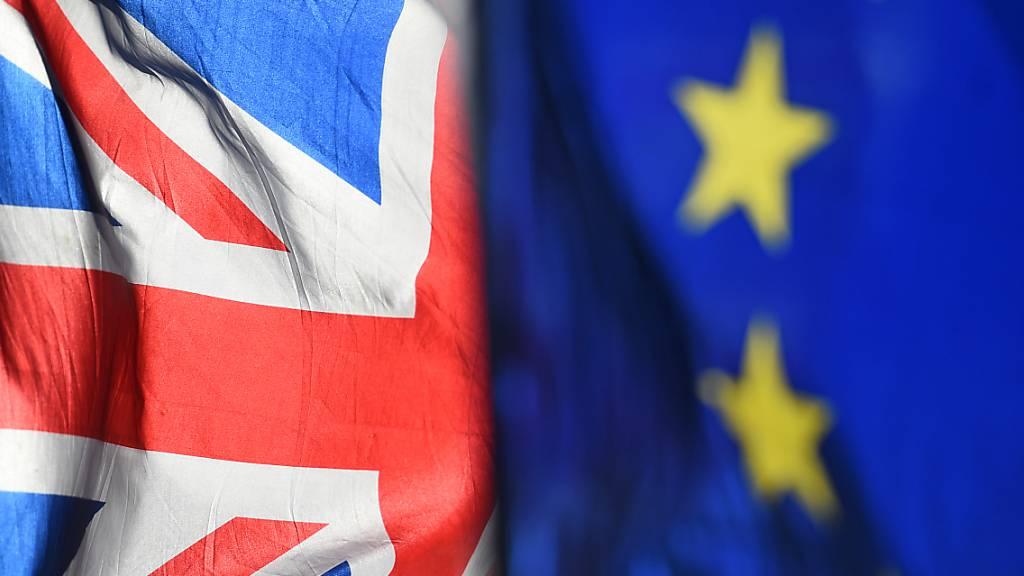 Eine Flagge der Europäischen Union und eine Flagge von Grossbritannien wehen vor dem Parlament in Westminster.
