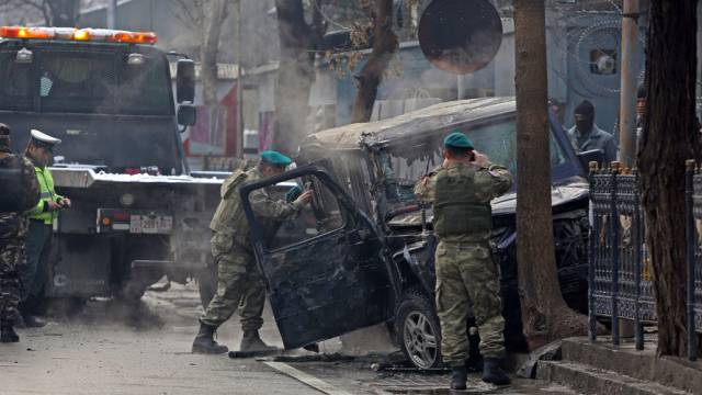 Türkische NATO-Soldaten untersuchen ein beschädigtes Auto vor Ort