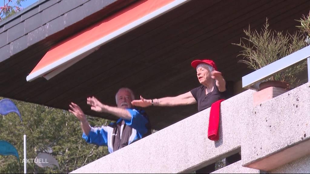Senioren halten sich mit Turnübungen auf Balkon fit